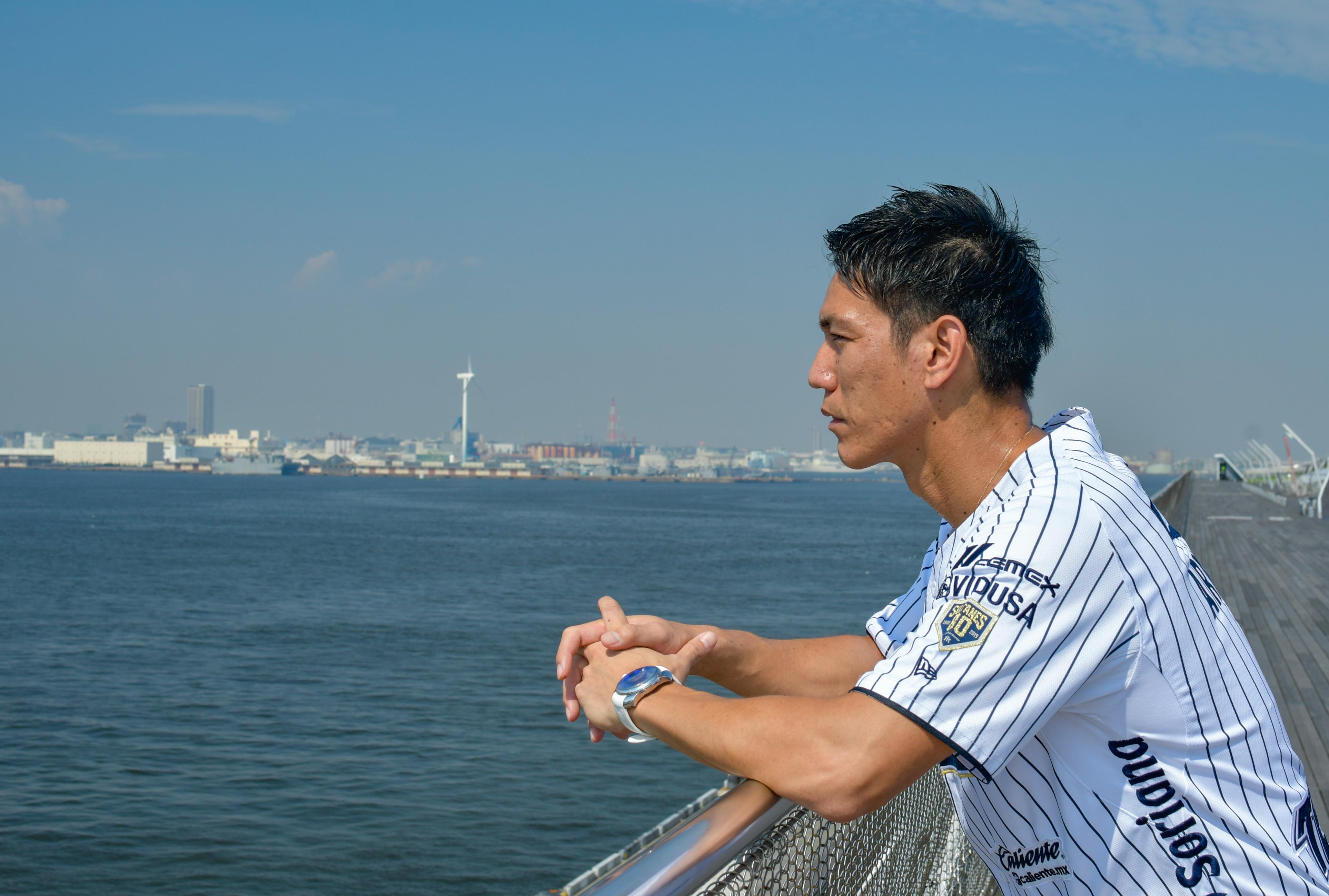 元・横浜DeNAベイスターズの荒波翔さんが海を背景に座っている所を横から撮った写真