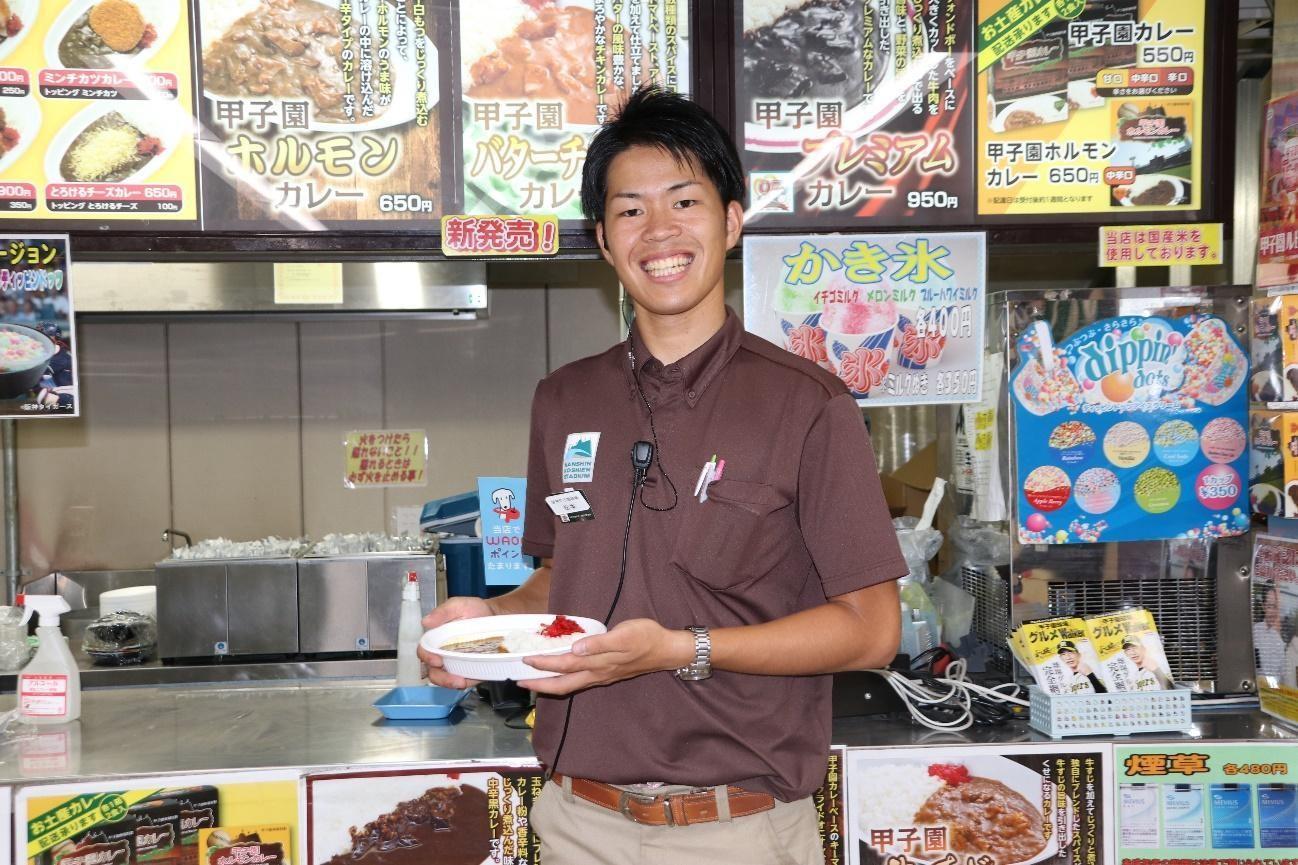 甲子園カレーともに笑顔をみせる店舗の担当者・松本さん
